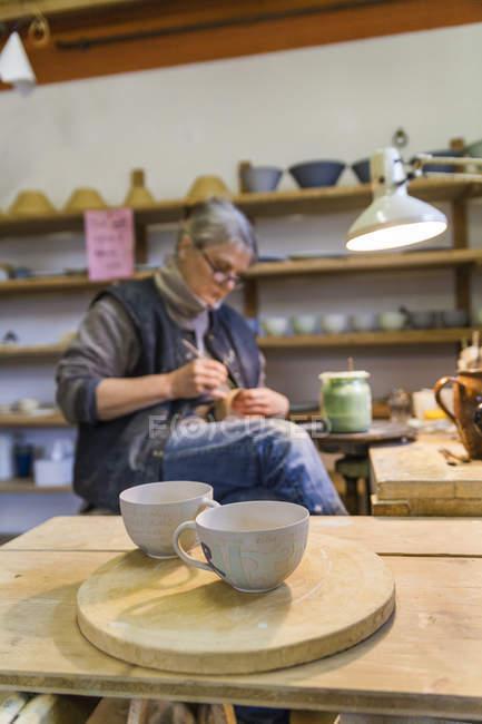 Potter в майстерні з чашки на передньому плані — стокове фото