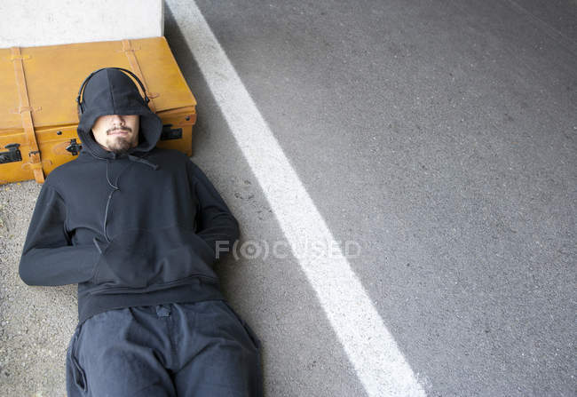 Man wearing hooded jacket sleeping beside lane — Stock Photo