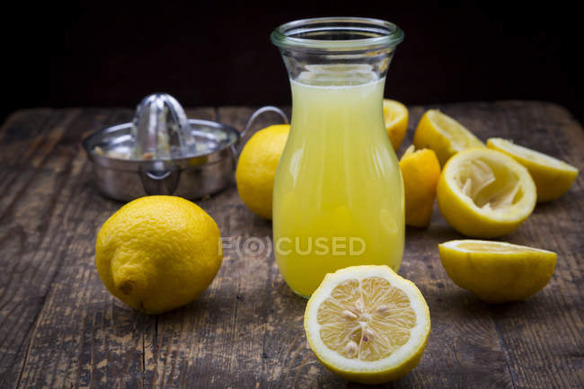 Jugo de limón recién exprimido, limones orgánicos, exprimidor del limón - foto de stock