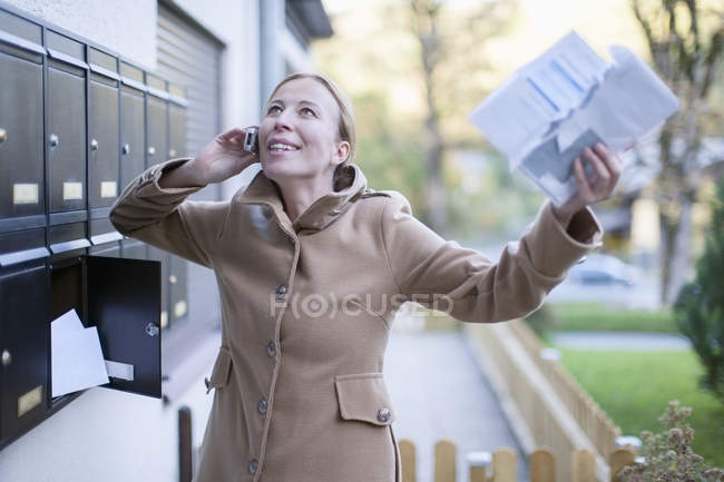 Happy woman telephoning with smartphone holding letter in her hand — Stock Photo