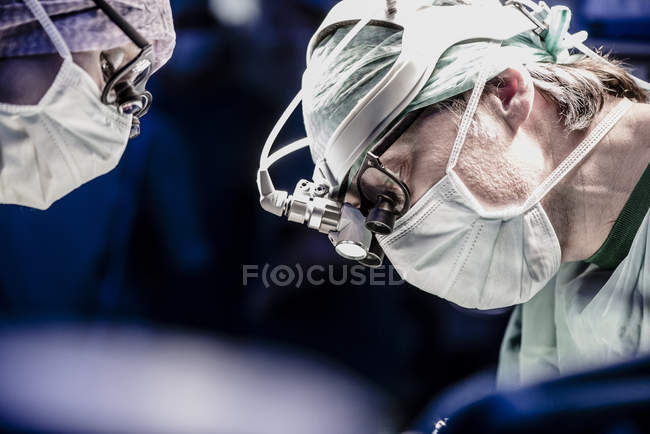 Cropped portrait of two surgeons during a surgery — Stock Photo