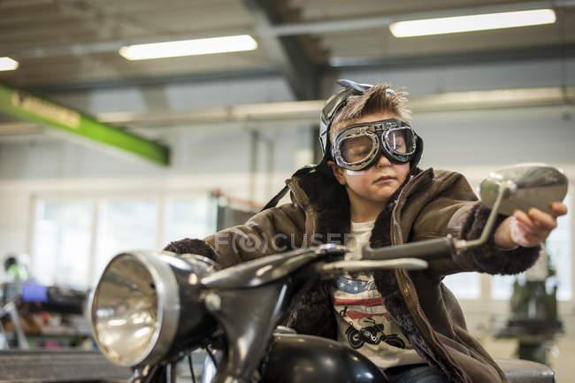 Garçon dans googles prétendant conduire vélomoteur vintage — Photo de stock