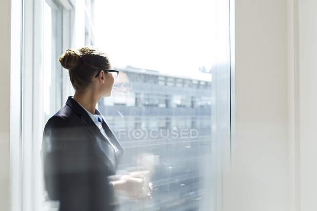 Imprenditrice che guarda fuori dalla finestra — Foto stock