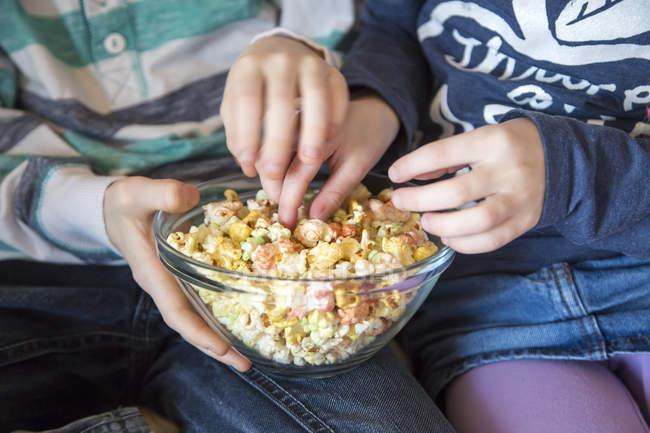 Mains du garçon et de fille prendre couleur popcorn — Photo de stock