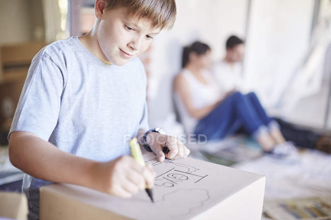 Boy writing on a cardboard box box in new house with parents on background — Stock Photo