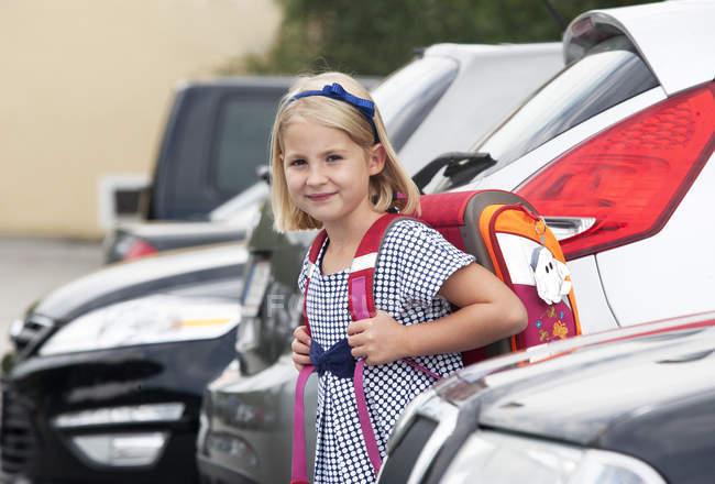Retrato de menina com bolsa escola, entre os carros do estacionamento — Fotografia de Stock