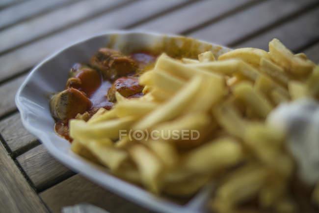 Currywurst y papas fritas con mayonesa en el plato - foto de stock