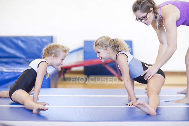 Тренер с девочками гимнастика упражнения на этаже — стоковое фото
