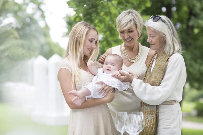 Trois femmes se rassemblent autour du bébé à l'extérieur — Photo de stock