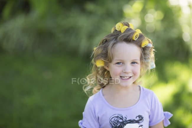 Улыбающаяся цветочница с бигудями в волосах — стоковое фото