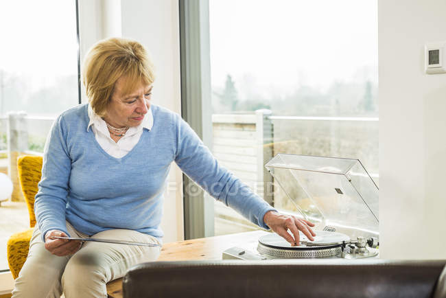 Senior woman at home putting record on record player — Stock Photo