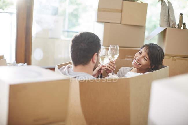 Casal casa em movimento sentado em uma caixa e copos de vinho clinking — Fotografia de Stock