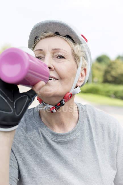 Portrait of senior woman with cycling helmet and drinking bottle — Stock Photo