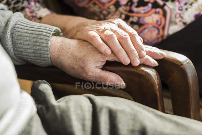 Hands of senior couple on arm rest — Stock Photo