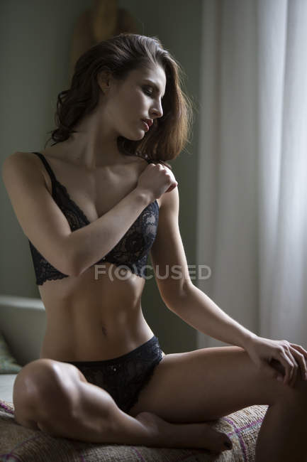 Sensual young woman in lingerie sitting on couch - foto de stock