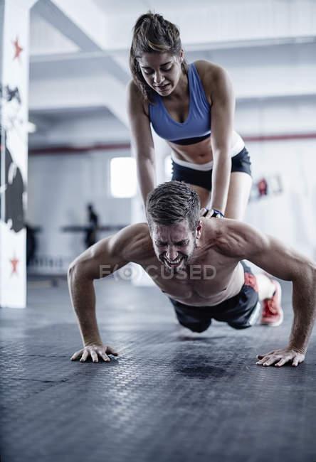Mann tut Liegestütze mit Frau kniend auf dem Rücken — Stockfoto