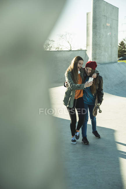 Girls with cell phone in skatepark — Stock Photo