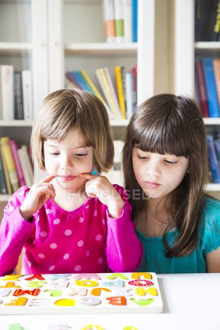 Portrait de deux sœurs assises avec puzzle alphabet en bois — Photo de stock
