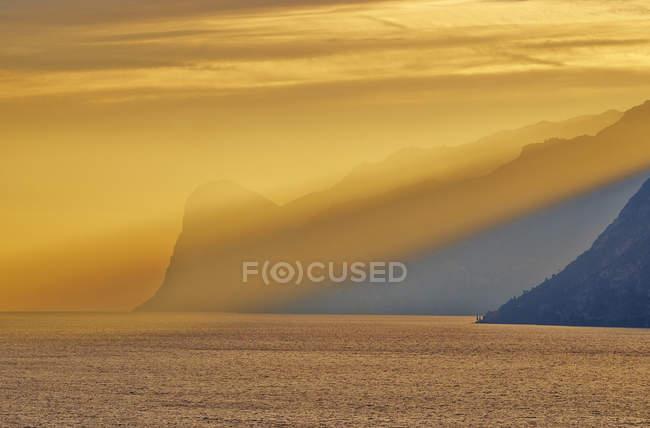 Italie, Torbole, Lac de Garde avec montagnes au coucher du soleil — Photo de stock
