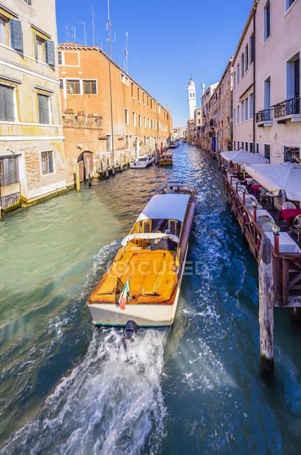 Itália, Veneza, barcos em um canal e fileiras de casas antigas — Fotografia de Stock