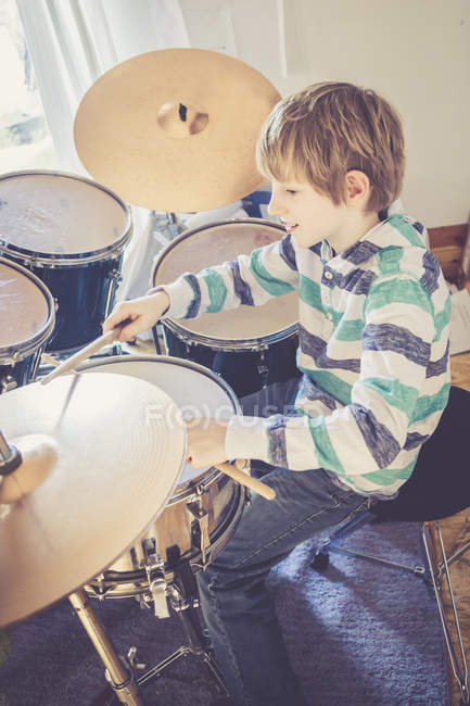 Cute caucasian boy playing drums at home — Stock Photo