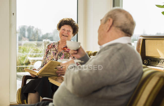 Senior couple with photo album drinking coffee at home — Stock Photo