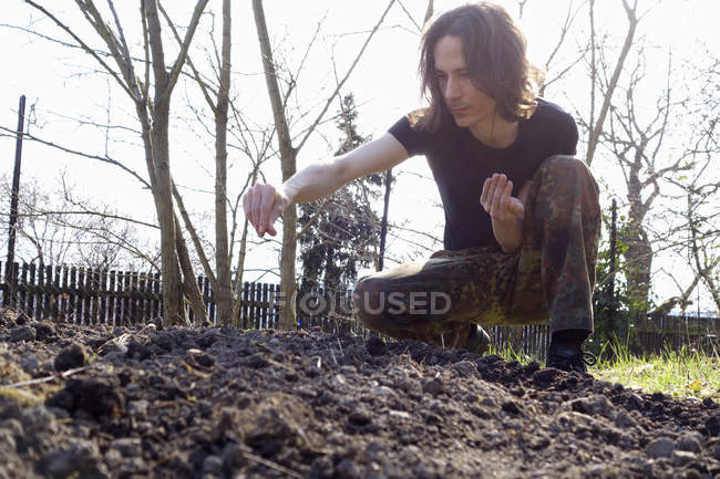 Man sowing in organic garden — Stock Photo