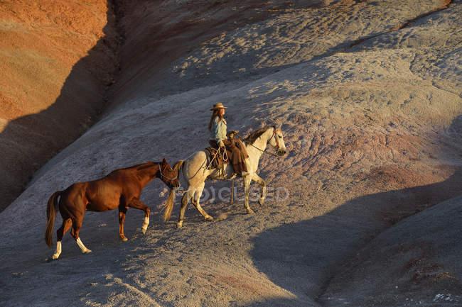 USA, Wyoming, cowgirl con due cavalli nei calanchi — Foto stock