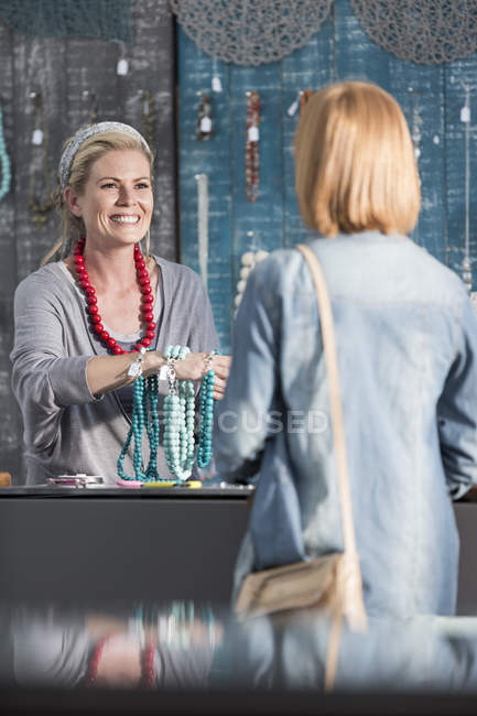 Woman showing beads and necklaces to a customer — Stock Photo