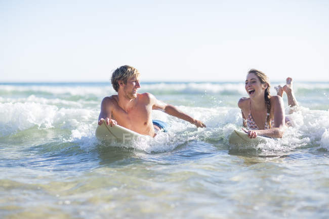 Feliz joven pareja acostada en tablas de surf en el mar - foto de stock