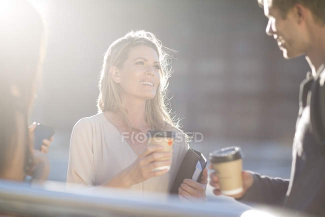 Three people with coffee to go talking in city — Stock Photo
