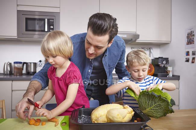 Pai, preparar os alimentos na cozinha com as crianças — Fotografia de Stock