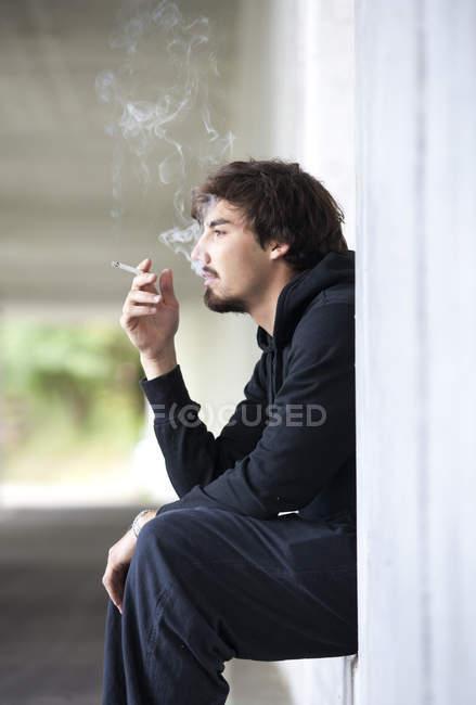 Joven fumando cigarrillo - foto de stock