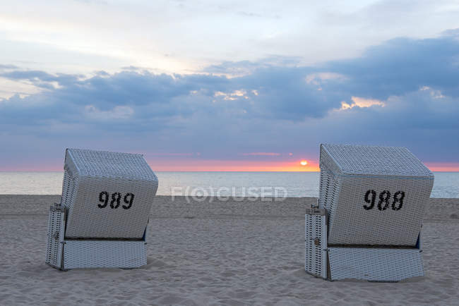 Germany, Schleswig-Holstein, Sylt, Westerland, hooded beach chairs on beach at sunset — Stock Photo