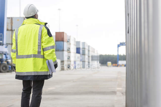 Man wearing safety jacket at container port — Stock Photo