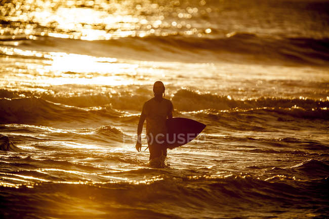 Indonesia, Bali, man with surfboard at twilight — Stock Photo