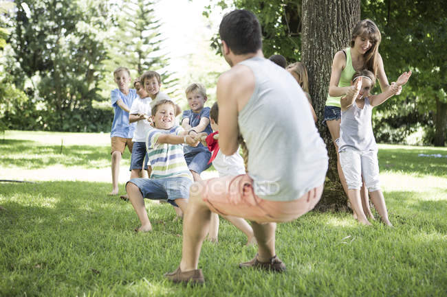 Niños y jóvenes compitiendo en tira y afloja - foto de stock