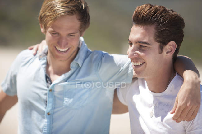 Two friends arm in arm on the beach — Stock Photo