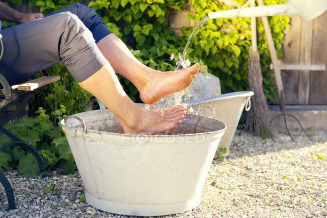 Laughing man taking footbath in a garden — Stock Photo