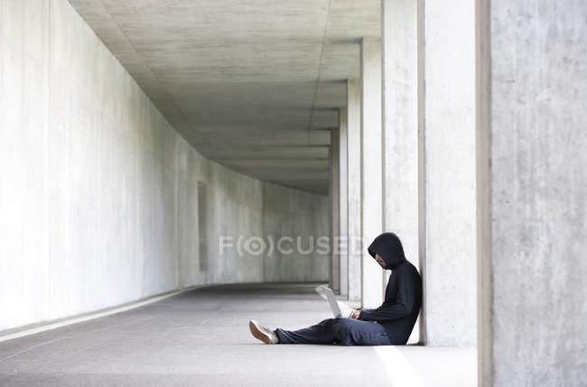 Hacker con portátil sentado en un aparcamiento subterráneo - foto de stock