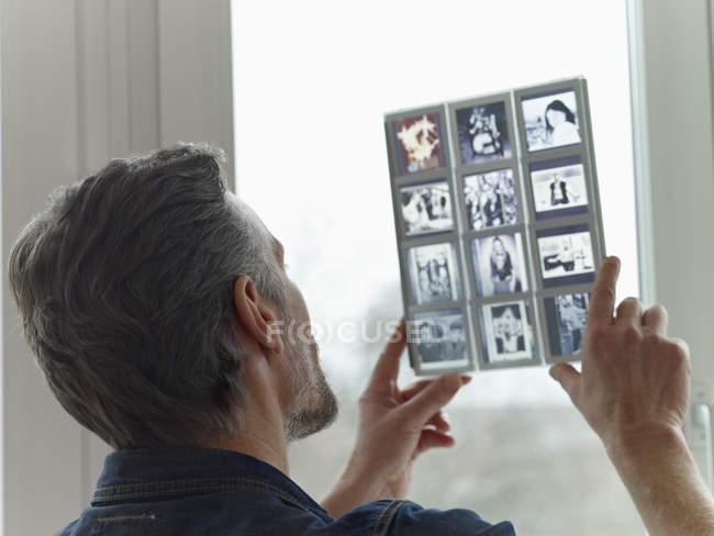 Mature man looking at old slides — Stock Photo
