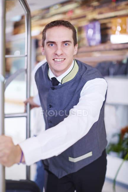 Готель bell хлопчика в фойє з багажем кошик — стокове фото