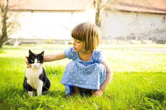 Little girl stroking cat on a meadow — Stock Photo