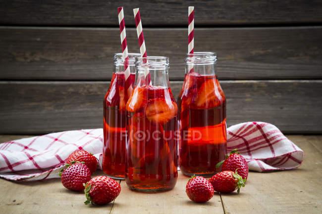 Closeup of three glass bottles of homemade strawberry lemonade and fresh strawberries — Stock Photo