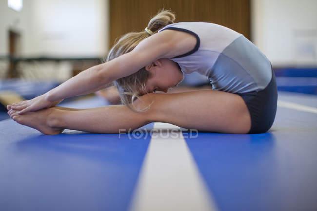 Girl doing gymnastics exercise on floor — Stock Photo