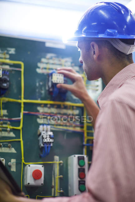 Electrician testing switch board on construction site — Stock Photo