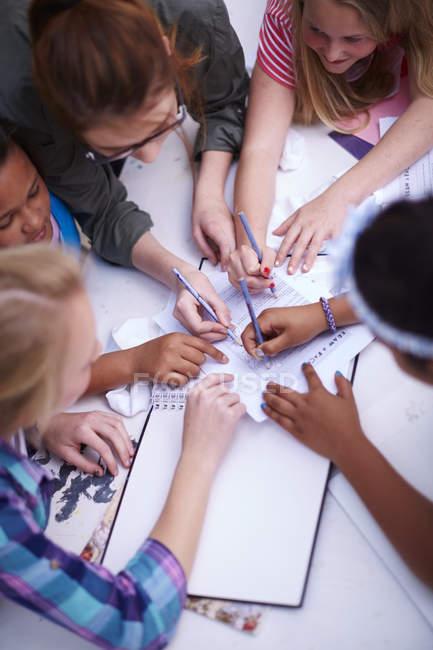 Insegnante e studentesse che scrivono insieme su carta — Foto stock