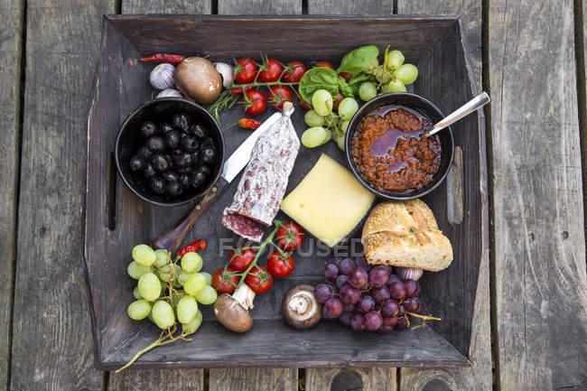 Различные итальянские закуски на деревянный поддон над столом — стоковое фото