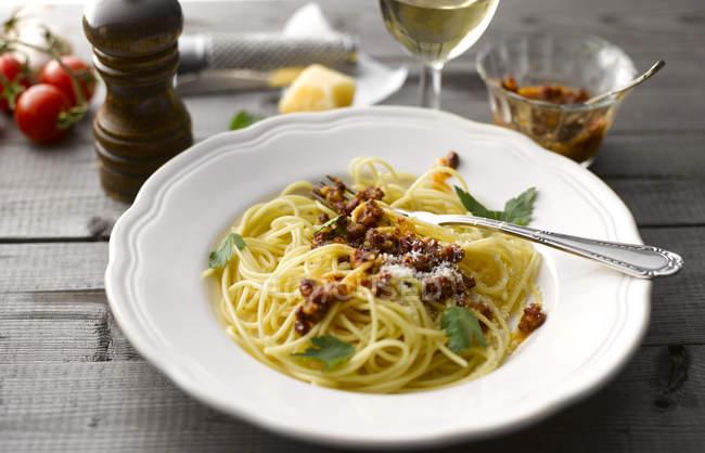 Блюдо из спагетти с томатным соусом песто и тертым сыром пармезан — стоковое фото