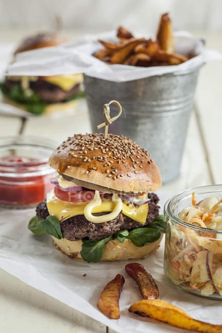 Hamburguesa casera con queso, ensalada de col y papas fritas - foto de stock